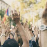 Protestors raising their arms in a crowd / Image: Unsplash