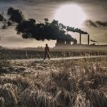 A person walking across a field with thick smoke coming out of a factory in the background / Image: Unsplash