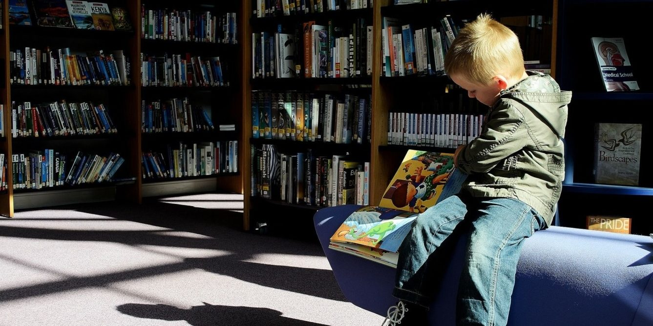 Small child sitting in a library