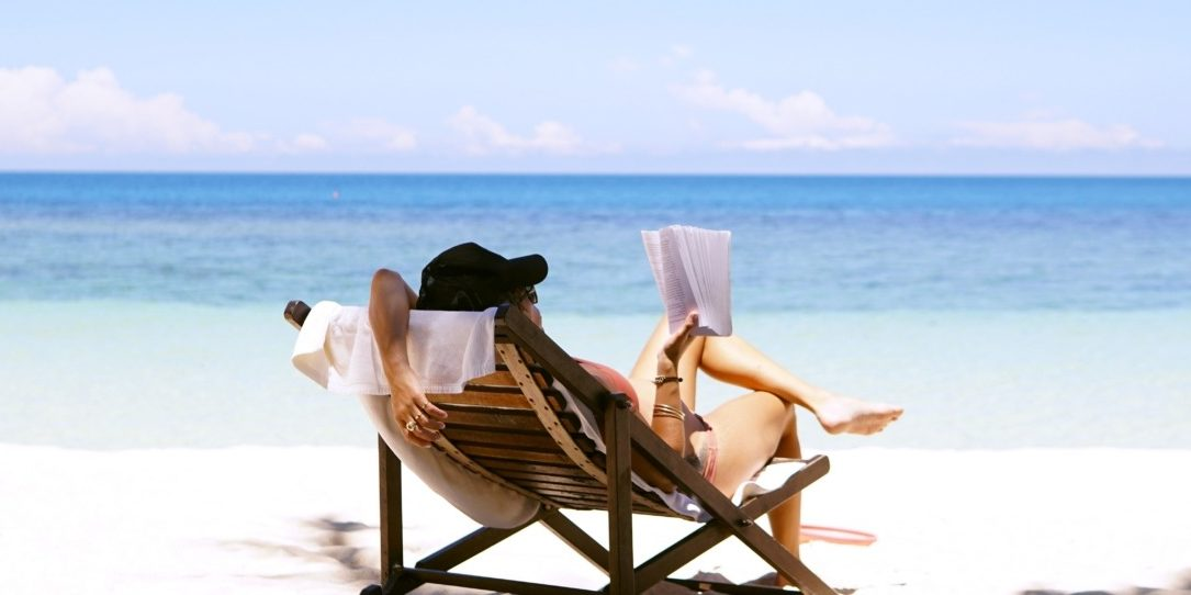 Woman reading books on a beach holiday