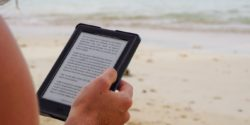 Person reading a kindle on beach holidays