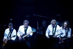 dark image of members of the Eagles on stage
