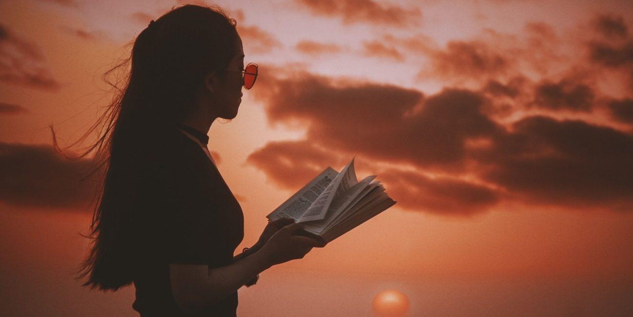 Girl reading against summer sunset