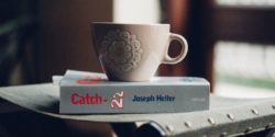 Catch-22 on a table with a mug - translation