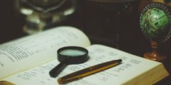 Magnifying glass and pen on historical book