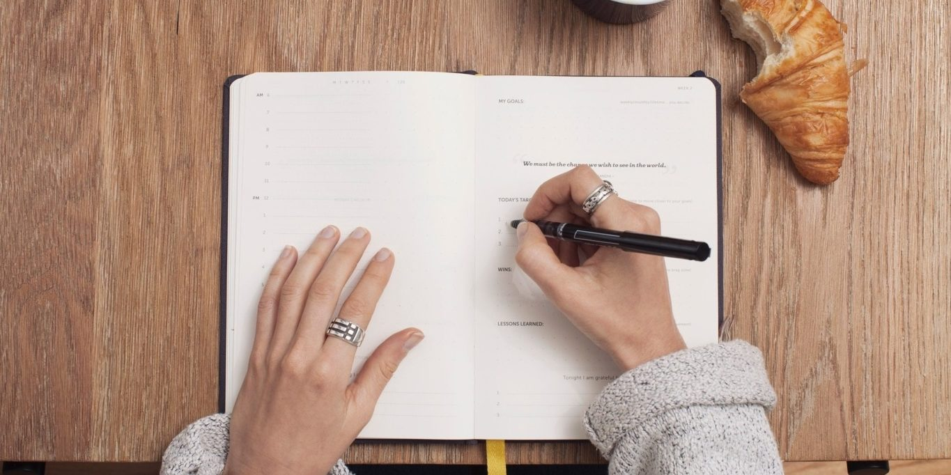 Author writing in a notebook
