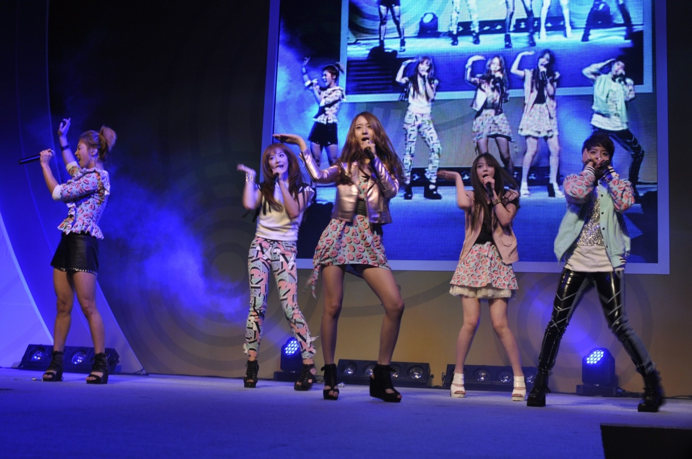 f(x) band on stage, blue lit stage, high energy performance