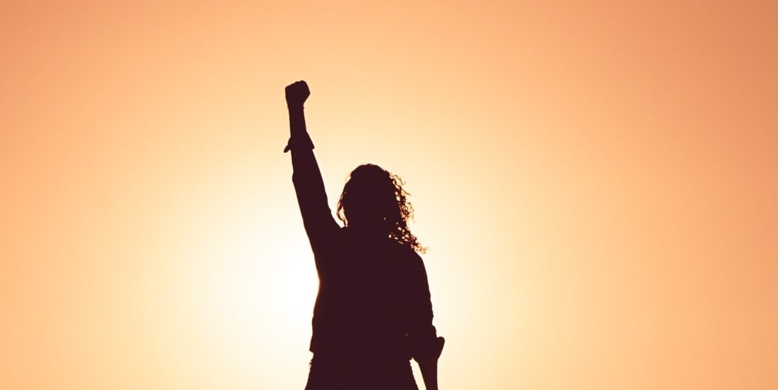Woman raising fist against sunset - courage