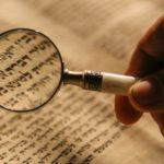 Magnifying glass held over book