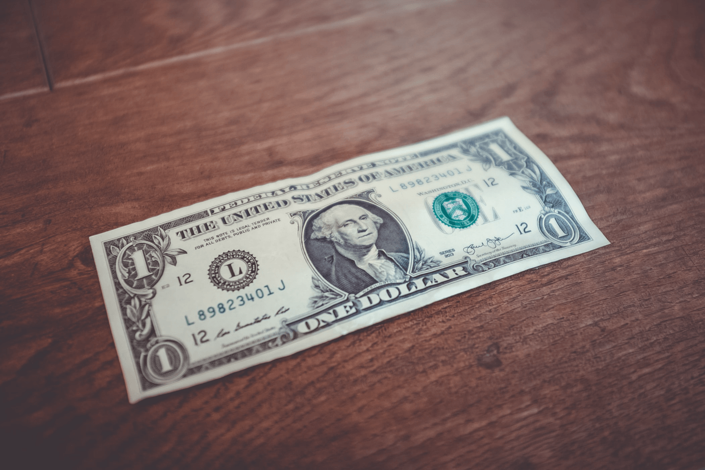 Dollar bill on a wooden surface