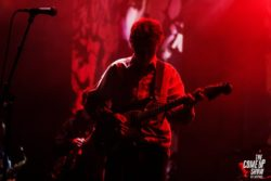 king krule on stage, red background, with a guitar
