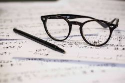 A pair of glasses and a pen resting on composition.