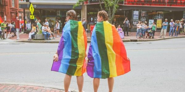 two women with LGBTQ+ flag