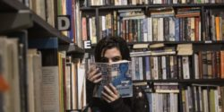girl covering face with book - bookseller